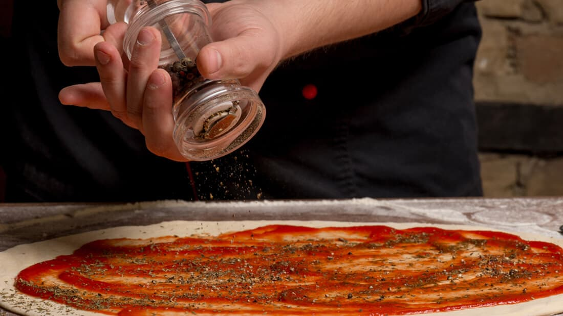 A man is spreading pepper on a pizza covered with tomato sauce